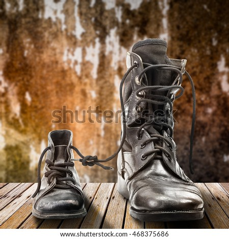 Combat boots for adult and kid on wooden table in concept of father and son in family