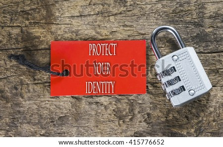 Combination number padlock on wood background with Protect Your Identity written on label tag