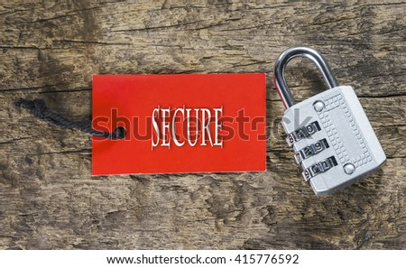 Combination number padlock on wood background with secure written on label tag - stock photo
