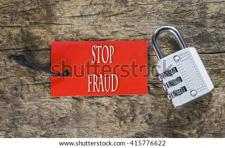 Combination number padlock on wood background with Stop Fraud written on label tag - stock photo