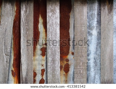 combination of wood and galvanised sheet metal construction materials texture rusty metal sheet and rough wood surface on a country house fence in THAILAND - stock photo