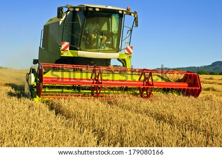 Combine harvester at work harvesting a field of wheat. - stock photo