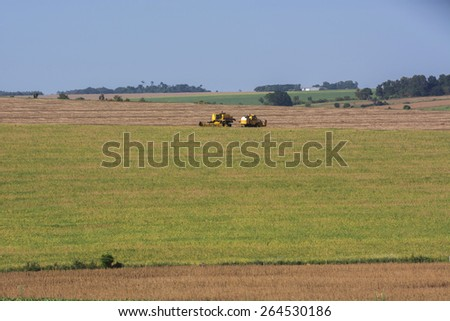 Combine harvester harvesting soybean at field - stock photo