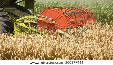 Combine harvester in action on wheat field, close-up shot of combine header - stock photo