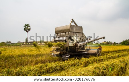 combine Harvester in rice field - stock photo
