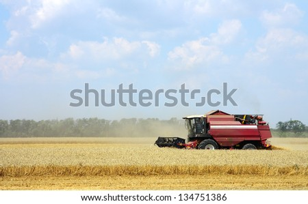 Combine harvester working in a field - stock photo