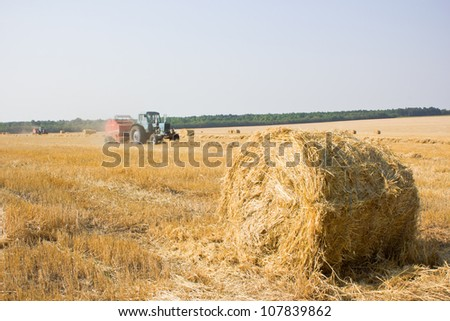 combine harvester working on field with straw bales  in Ukraine - stock photo