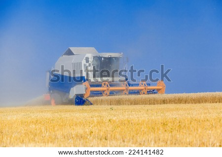 Combine harvester working on sunny summer day. - stock photo