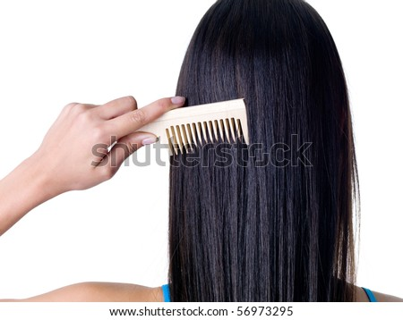 Combing healthy long straight female hair - close-up - stock photo