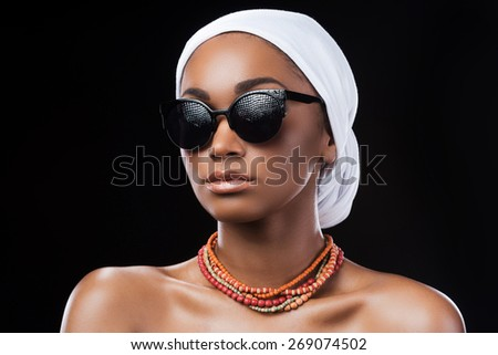 Combining fashion and traditions. Beautiful African woman wearing a headscarf and sunglasses while standing against black background - stock photo