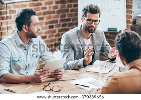Combining their expertise. Young handsome man in eyeglasses gesturing and discussing something while his coworkers listening to him sitting at the office table - stock photo