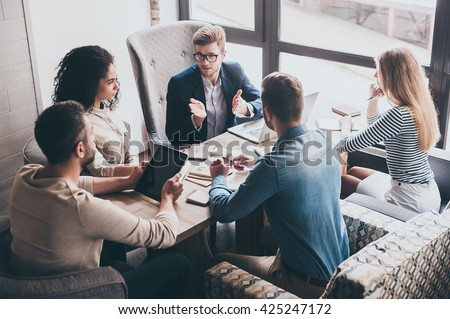 Combining their expertise. Young handsome man in glasses gesturing and discussing something with his coworkers while sitting at the office table - stock photo