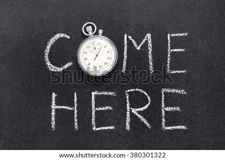 come here phrase handwritten on chalkboard with vintage precise stopwatch used instead of O