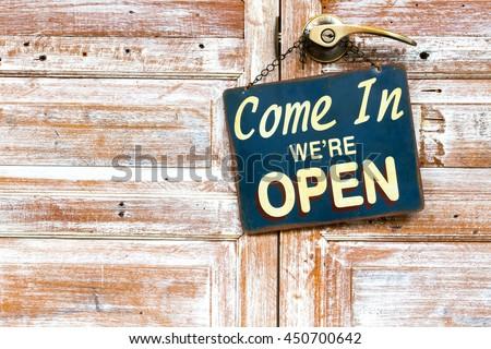 Come In We're Open on the wooden door, copyspace on the left. - stock photo
