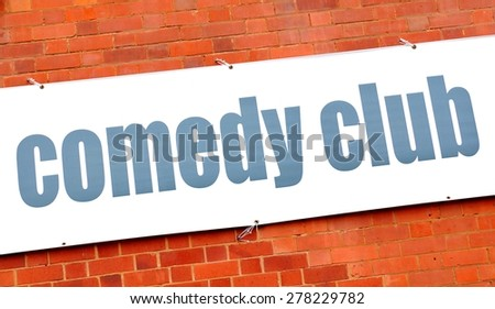 Comedy club sign against red brick wall - stock photo