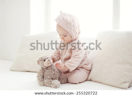 Comfort, sweet baby playing at home in white room near window - stock photo