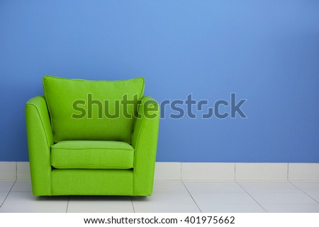 Comfortable armchair against blue wall background - stock photo