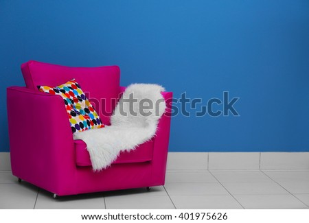 Comfortable armchair with pillow and blanket against blue wall background - stock photo