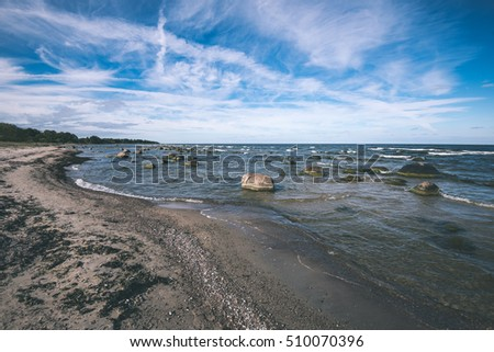comfortable beach of the baltic sea with rocks and green vegetation in summer - vintage film look