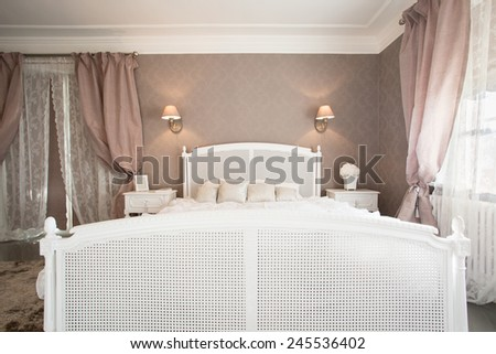 Comfortable bed in bedroom in romantic style - stock photo