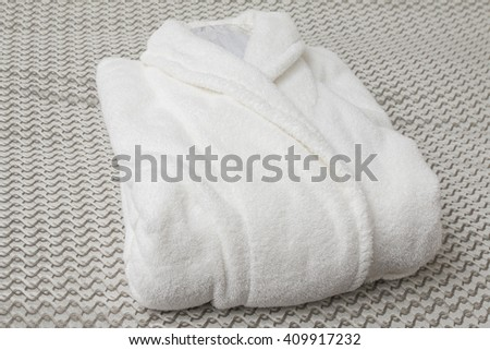 Comfortable bed with clean bathrobe in upscale hotel - stock photo