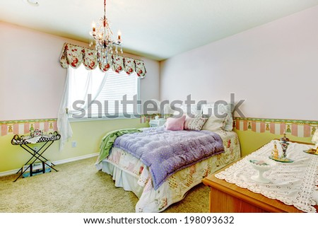 Comfortable bedroom with walls in pink and lime colors. View of bed with colorful bedding