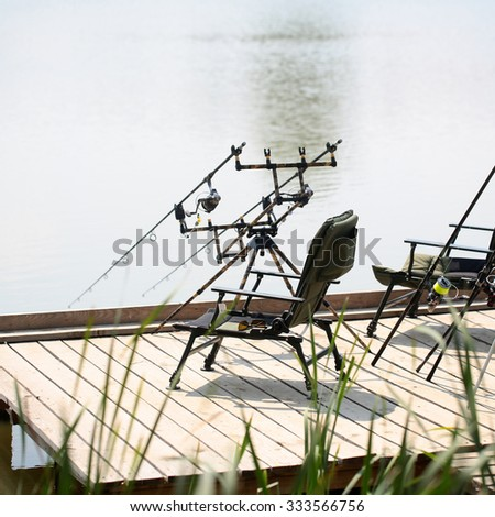 Comfortable black armchair and rod pod with carp carbon spinnings standing on pier in background of blue water of lake hobby outdoor angling male activity in summer, square picture  - stock photo