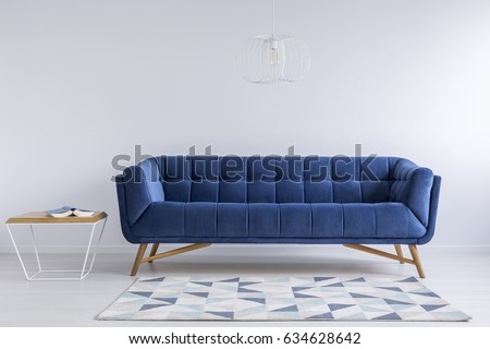 Comfortable Blue Couch And Wooden Coffee Table In Simple White Apartment