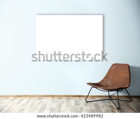 Comfortable chair and empty picture frame on blue wall background - stock photo