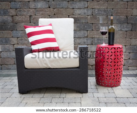 Comfortable Dark Wicker Patio Chair Outfitted with Plush Cushions Beside Modern Red Table with Bottle and Glass of Red Wine on Outdoor Stone Affluent Patio - stock photo