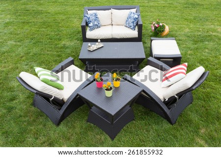 Comfortable deep modern garden furniture with stylish armchairs and a two seater settee arranged on a neat manicured green lawn with tables decorated with potted plants, high angle view - stock photo