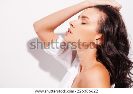 Comfortable in her own skin. Side view of beautiful young woman undressing and keeping eyes closed while standing against white background   - stock photo