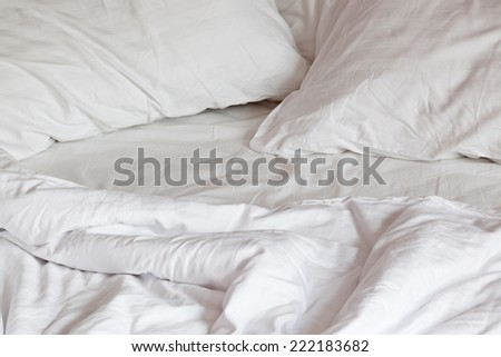 Comfortable, messy bed with pillows and duvet  - stock photo