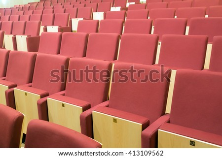 Comfortable seats with red upholstery in audience hall - stock photo