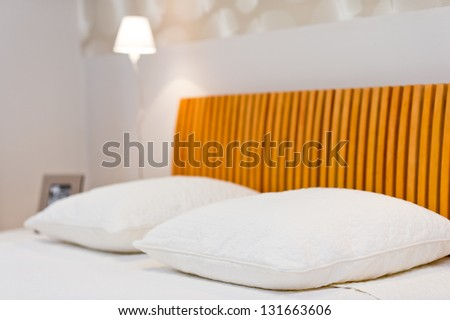 Comfortable soft pillows on the bed with lamp in the background - stock photo