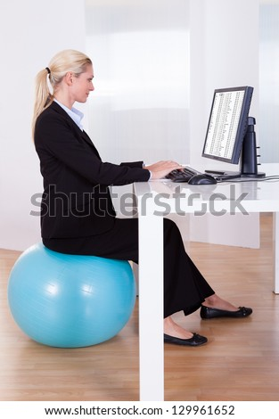 Comfortable working environment with an elegant young blonde office worker sitting on a pilates ball