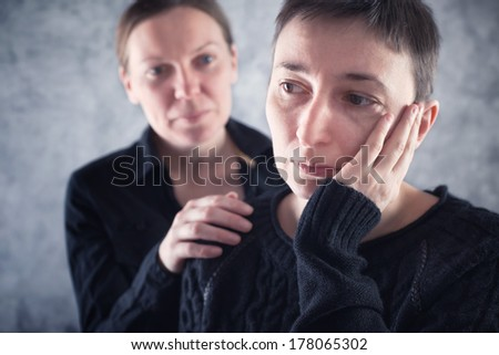 Comforting friend. Woman consoling her sad friend with hand on shoulder. - stock photo