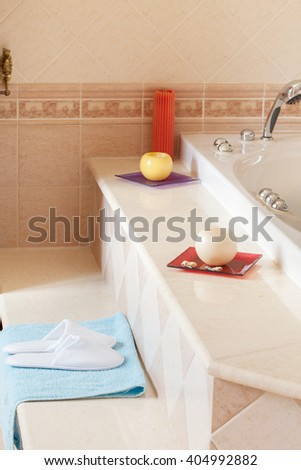 Comfy spa-style slippers on blue towel besides the jacuzzi bathtub in home bathroom. - stock photo