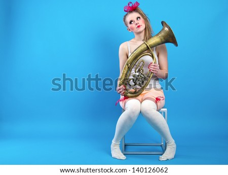 Comic girl with a trombone in hand is sitting on a blue background. - stock photo