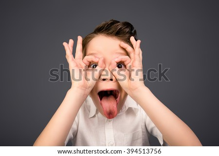 Comic little boy holding hands like glasses and showing tongue - stock photo