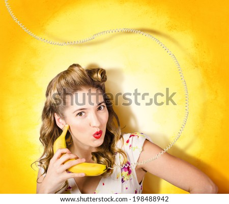 Comic photo of a retro pin-up girl with olden day hair rolls making funny surprise expression when talking bananas through fruit phone on yellow grunge wall. Gossip and converse - stock photo