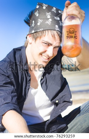 Comical And Witty Concept Of A Pirate Holding Up A Bottle Of Rum With A Skull And Crossbones Sign While Celebrating His Demise In A Cheers To Death Concept - stock photo