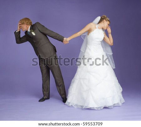 Comical emotional groom and the bride holding hands on violet background - stock photo