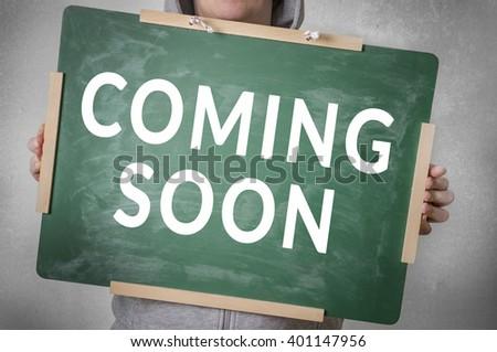 Coming soon text written on chalkboard - stock photo