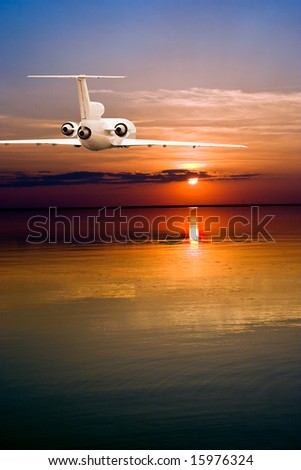 Commercial airliner flying over water to sun - stock photo