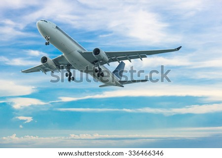 Commercial airplane flying with blue sky background - stock photo