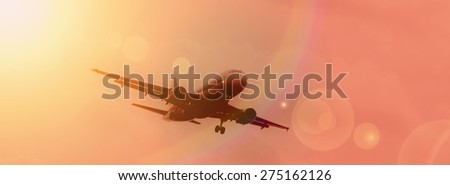 Commercial airplane landing at sunset. - stock photo