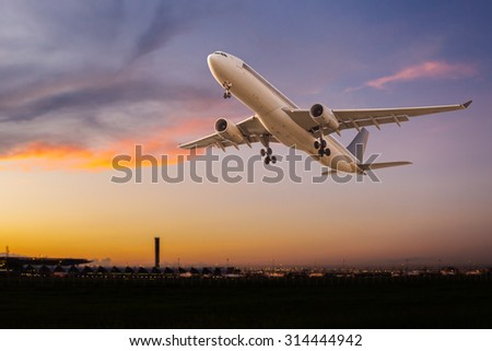 Commercial airplane take off at sunset - stock photo