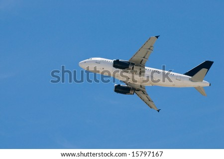Commercial airplane taking off, against clear blue sky - stock photo