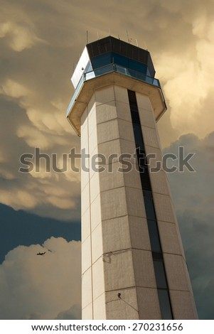 Commercial Airport Control Tower from close up perspective with large thunderstorm developing overhead and commercial aircraft flying past the storm illustrating the danger of weather in air travel.  - stock photo